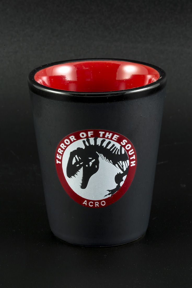 """Acro"" Black/Red Shot Glass. Featuring the dinosaur Acrocanthosaurus, the ""Terror of the South."" $7"