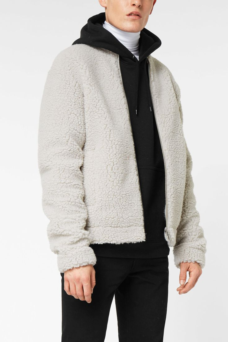 The Wes Zip Sweater is a boxy warm piece made of a faux shearling material. It has a high neck, a metallic zipper along the front, two pockets, dropped sho