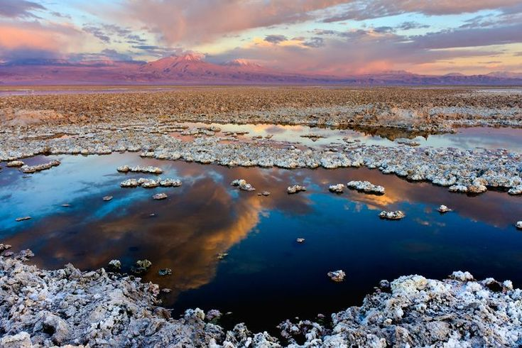 Salar de Atacama is the largest source of lithium active in the world today and is the lightest elemental metal in the periodic table. Lithium is used in the production of batteries as well as in soldering and for lubrication. At the horizon, the Licancabur volcano (19,400 ft or 5,913 m) can be seen.