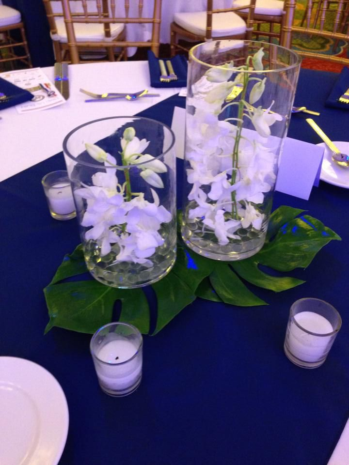 White dendrobium orchids in cylinder vases atop monstera leaves...