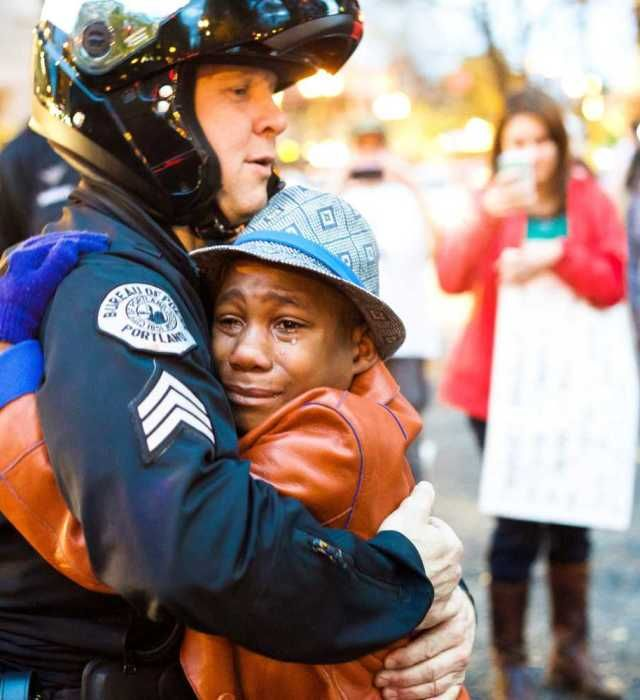 "People protest a grand jury's decision to not indict a white police officer in the fatal shooting of an unarmed black teenager. A boy, Devonte Hart, holding a ""Free Hugs"" sign stood crying in front of a police barricade. A white police officer motioned for him to come closer. The officer then asked the boy for a hug — and they embraced, the boy's anguished face streaming with tears. Devonte hart, 12-year-old, said the moment was about ""listening to each other, facing fears with an open…"
