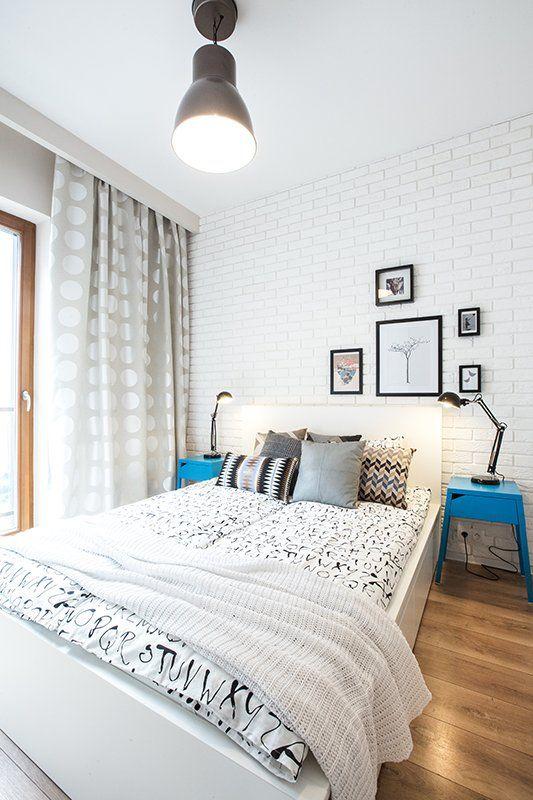 Ceglana ściana w sypialni jest tłem dla łóżka zasypanego poduchami w geometryczne wzory.