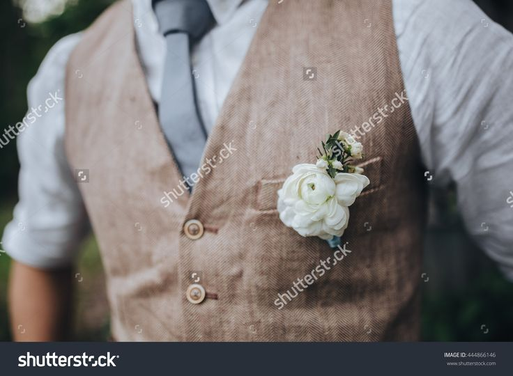 Wedding. The groom in a shirt and a waistcoat with a buttonhole is in the garden