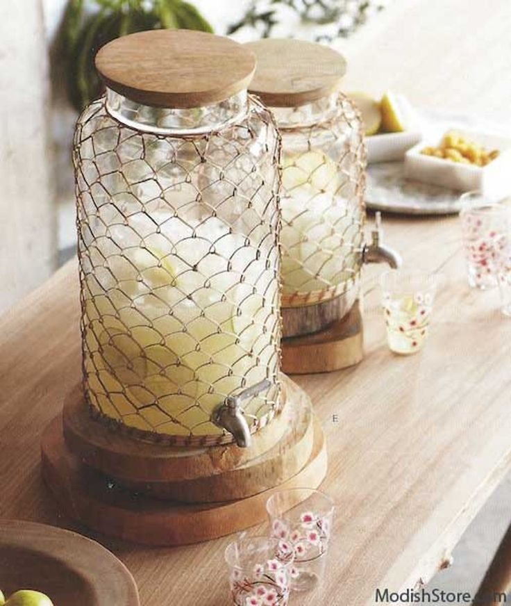 Glass beverage dispensers are finely dressed in delicate woven rattan sleeves. Each Roost Rattan Beverage Dispenser has a mango wood top and a stainless steel spigot.
