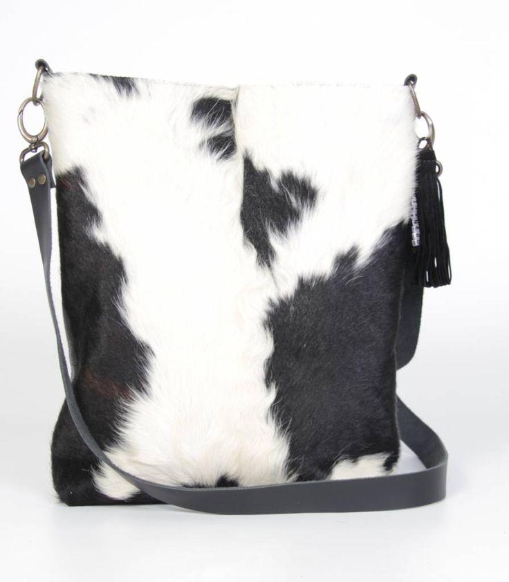 Stoere beugeltas ook wel dokterstas genoemd, van koeienhuid in zwart wit. Voorkant koeienhuid en de achterkant van stoer zwart runderleder. Achterop zit een een ritsvak en binnenin zit ook een ritsvak en een vak voor je mobieltje.