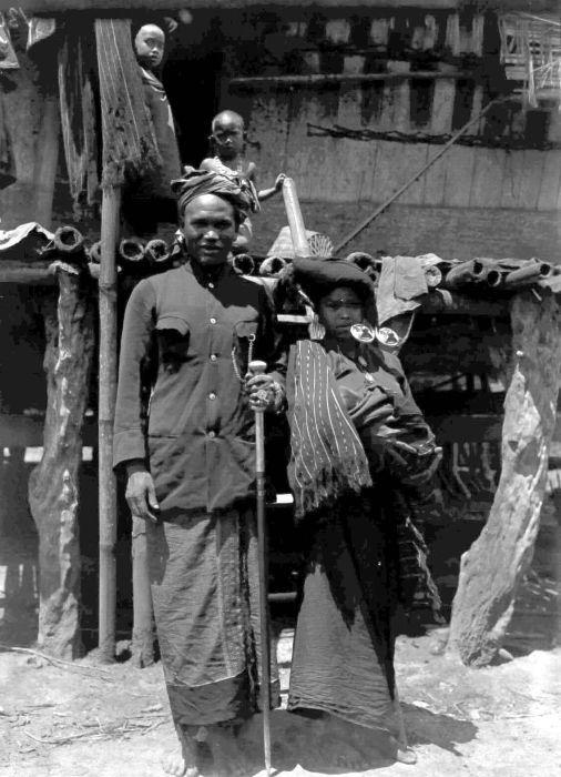 Karo people (Indonesia) | COLLECTIE TROPENMUSEUM De bekende Karo-Batak schaker Si Narser met zijn vrouw Karolanden Noord-Sumatra TMnr 10005391.jpg The woman is wearing a cloth called Gatip Ampar over her shoulder and silver earrings, padungpadung. The man is wearing possibly a Julu berjongkit or a Ragi Santik as a hip covering. From Karo Regency, circa 1914-1919.