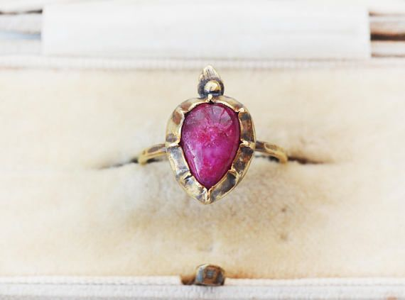 This is a dyed indian fuscia ruby heart set into antique georgian style pinch setting.  Highly rustic, oxidised and vintage style design. Patina and shine on the brass. The ruby was originally paler colour and has been dyed, that is why it is called dyed ruby. Vivid pink-red colour with