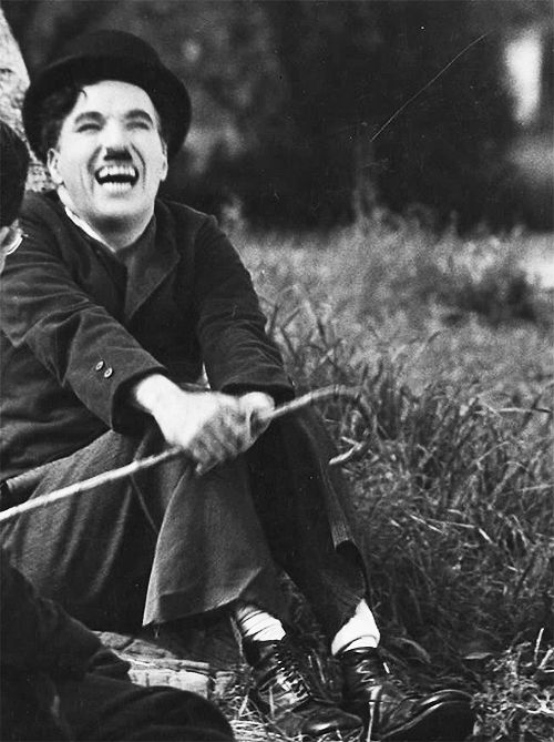 """This is not Charlie """"the tramp"""" but Charles Chaplin, something has genuinely struck his funny. He had such a beautiful and down to earth smile. On the set of """"Modern Times"""" 1935"""