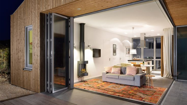 Design holiday home Vlieland by BNLA architecten. Thanks to the harmonica doors and the cantilevered awning, the connection between inside and outside is optimally used. Photography by Studio de Nooyer.