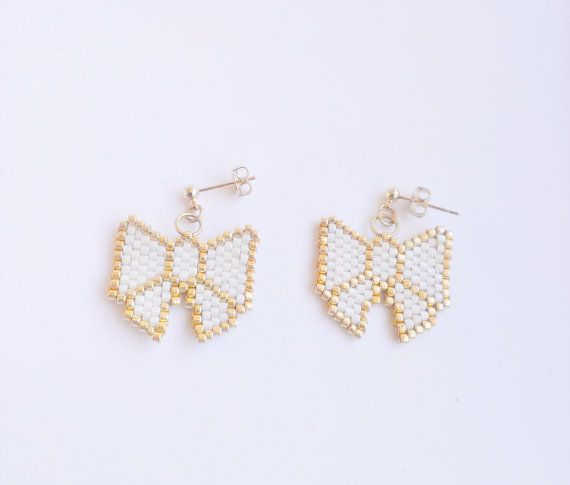 ~ Cute beaded white and gold bow earrings ~  This listing is for a pair of cute bow earrings in white and gold. It is hand woven with quality Japanese beads and set on gold colour earrings.  <Size> Length: Approximately 2.5cm include ear hook Bow: Approximately 2cm × 2cm  <Shipping> Orders will be shipped within 1-3 working days from Co.Louth, Ireland with expected delivery time of:  Within Ireland: 1-5 working days Outside Ireland: 1-3 weeks depending where you are located   If you have any…