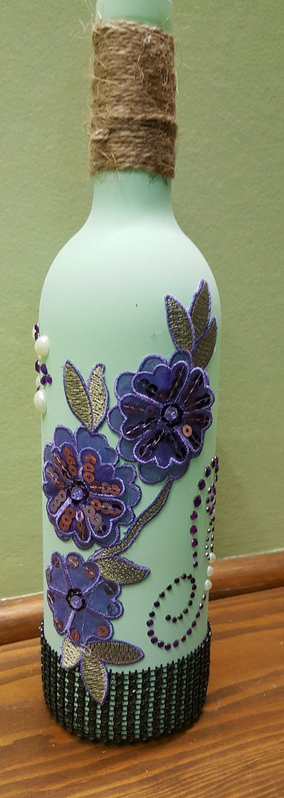 Mint green bottle decorated with black, purple & white embellishments A great gift item About 3 inches wide by 12 inches tall