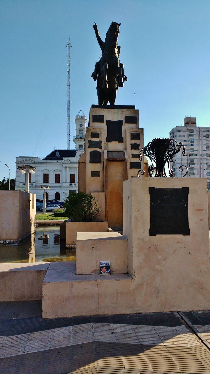 """El domingo 21 de enero de 2018, en la plaza de Azul (pcia. de Buenos Aires), mientras había un acampe en protesta frente a la Municipalidad (al fondo) por el cierre de Fabricaciones Militares, elidanora liberó """"El hombre del labio retorcido"""" de Arthur Conan Doyle."""