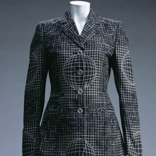 Black suit with fine white grid lines over the whole surface. At regular intervals, the grid morphs into a spherical pattern, producing an effect reminiscent of Op art or wireframe drawing for 3D computer graphics (CG). In the mid-1990s, high performance gaming machines like Playstation and consumer-oriented operating systems, especially Windows 95, became generally available, and ordinary individuals started to use digital technology such as CG and the Internet.