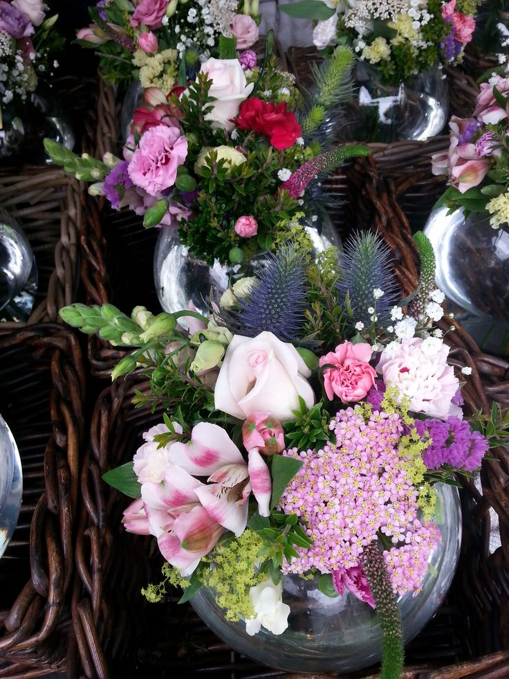 Beautiful corporate event table centrepieces - fab goldfish bowls filled with pretty pinks, purples and creams. http://www.isleofwightflowers.co.uk/