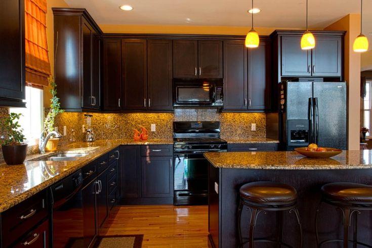 black cabinet black appliances dark bar stool granite countertop granite backsplash pendant lights light wood floor built in sink of Irresistible Kitchen with Black Appliances Ideas