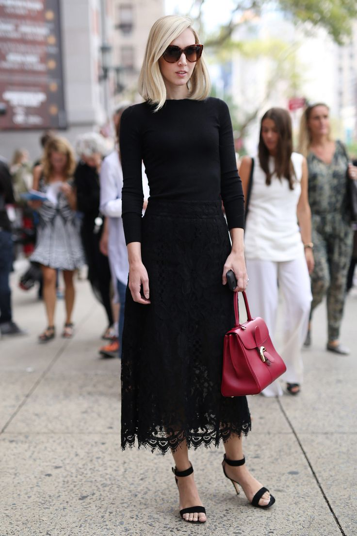 Jane Keltner de Valle in an all-black outfit with a lacy hem and a bright bag.