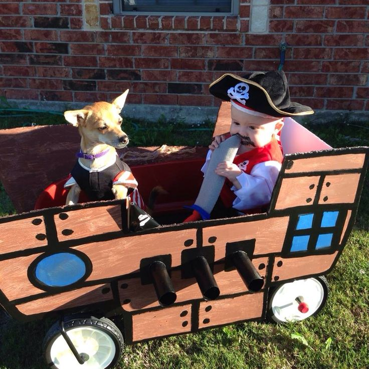 Diy pirate ship with painted foam board, hot glue, and toilet paper rolls for cannons. Homemade Pirate wagon. Halloween infant toddler pirate costume with matching dog costume. The other side has a wooden anchor purchased at Michael's craft store