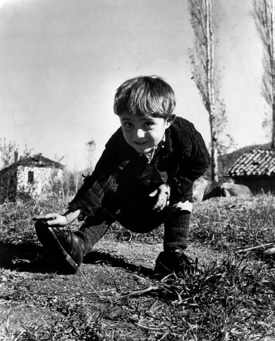 "David Seymour, Oxia ,Greece. 1949. Elefteria, the only child not evacuated from her remote village during the ravages of the civil war there, receives her first pair of shoes from UNICEF. Chim wrote his own caption for the picture: ""For a long time four-year old Elefteria just stared at the new shoes. Finally, her grandmother was allowed to put them on her feet. Then the ice was broken. Elefteria ran through the village, laughing with delight. Her happiness was absolutely perfect."""