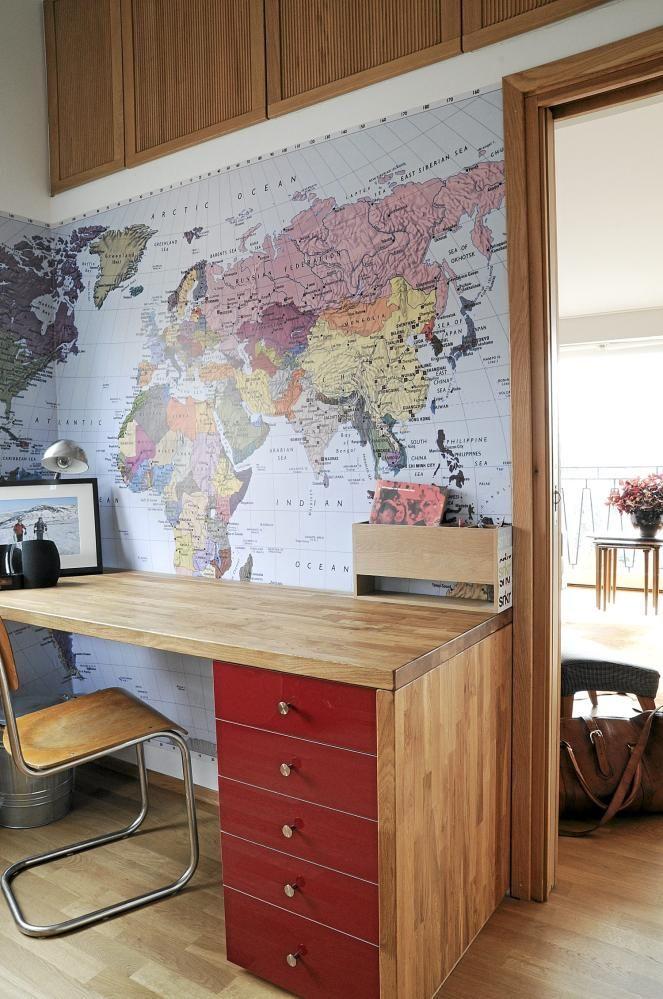 """Ved arbeidsplassen har halve veggen blitt """"tapetsert"""" med et verdenskart."""
