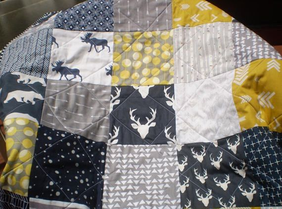 This adorable rustic woodland themed patchwork baby quilt measuring 36 X 48 in navy blue, mustard yellow and grey featuring deer, stag, bears, moose as well as arrows and trees would be perfect for the nursery for a boy or a girl; newborn, infant or toddler.(FYI: crib mattress measures