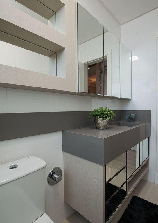 No banheiro dessa suíte, o padrão neutro se manteve, com bancada em marcenaria branca e tampo em silestone cinza. O armário aéreo com portas deslizantes em espelho é complementado por nichos com fundo espelhado.