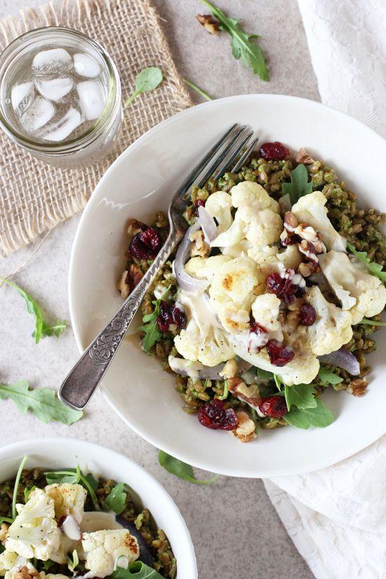 Recipe for healthy roasted cauliflower pesto farro bowls. With pesto coated whole grain farro, roasted veggies and tahini sauce!