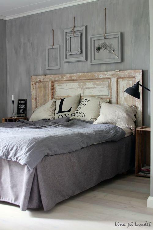 parede cinza na decoração do quarto com molduras vazias na mesma cor, cabeceira da cama com porta antiga