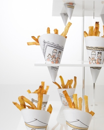 Pommes frites dusted with sea salt, by Callahan Catering (callahancatering.com), were served at the gallery event in paper cones featuring Darcy's illustrations.