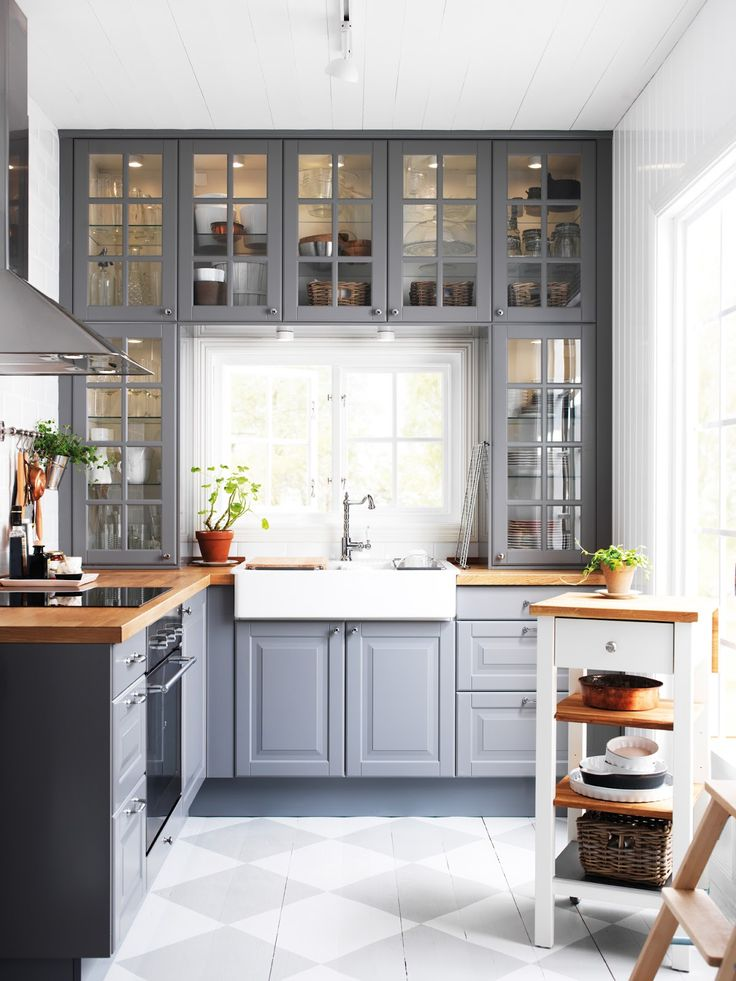 Ikea grey cabinets, option to paint the floor to save money, love the old window look to the upper cabinets, can be country and elegant more news read here: http://kitchencarcasses.net I like the color scheme and glass fronts in this kitchen.
