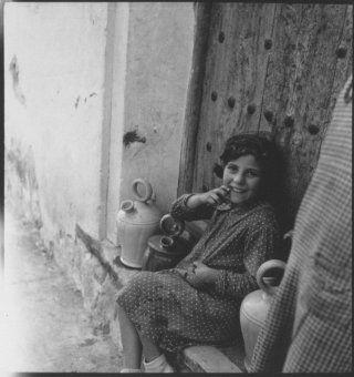 KATI HORNA .1937 Niña de Madrid, con vestido de lunares sentada a la puerta de una casa junto a varios botijos.