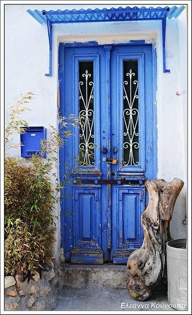 Porta dupla de madeira com janelinhas de vidro e metal. A cor...azul do céu.