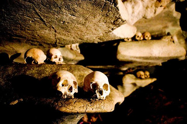 "https://flic.kr/p/kt3TV | cave grave in tana toraja | in tana toraja, everything revolves around death. the graves can be very sophisticated yet sometimes, long after the coffins are destroyed by time, people gently place bones along natural cave ""racks"". often, the bones are offered cigarettes or various offerings. this is supposed to prevent dead ancestors from bringing bad luck and otherwise making the lives of the living miserable."