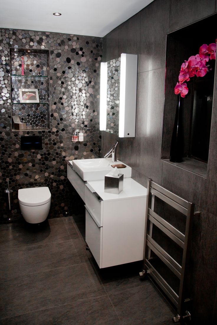 Stunning guest restroom with a futuristic feel featuring pebble mosaics, wall mounted iDock & Digital radio, wall hung toilet, illuminated mirror cabinet and brushed steel radiator. Copyright The Designer Knowledge. Photo by Ani Evans Photography.