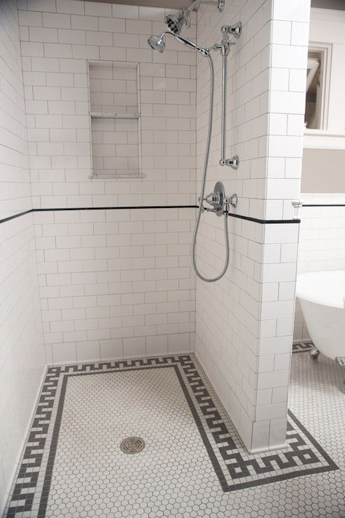Wet room style bathroom with walk-in shower enclosure tiled in white subway tile with a black pencil tiled border and recessed tiled shelves beside the adjustable shower head.