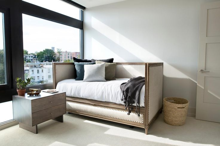 The upholstered daybed bench in this modern guest bedroom offers a comfy place for visitors to take an afternoon nap or enjoy the view by the window. A sleek small nightstand serves as handy storage space, while the large picture windows fill the space with natural light.