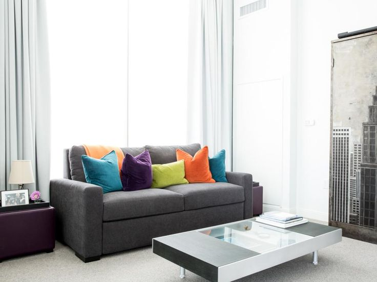 Jewel-toned throw pillows add a burst of color to this gray and white living room. A plum storage ottoman doubles as a side table, while a sleek coffee table keeps a low profile in front of the boxy gray sofa. A cityscape art piece hints at the home's urban setting.