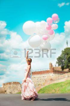 globos bodas: feliz novia en vestidos de novia elegantes asimiento globos día de verano al aire libre, foto de cuerpo entero, la fortaleza de Belgrado en el fondo
