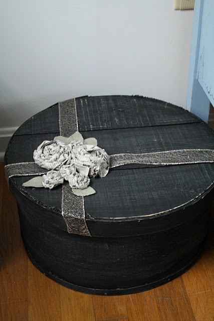 A cheese box decorated with ribbon ... and roses made from newspaper!