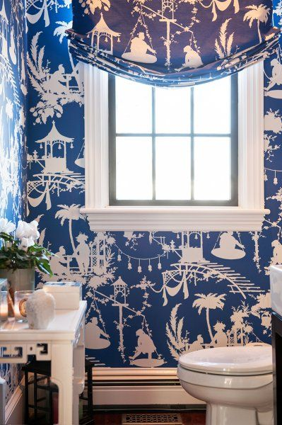 Chinoiserie style powder room clad in Thibaut South Sea Wallpaper in Navy which frames large .