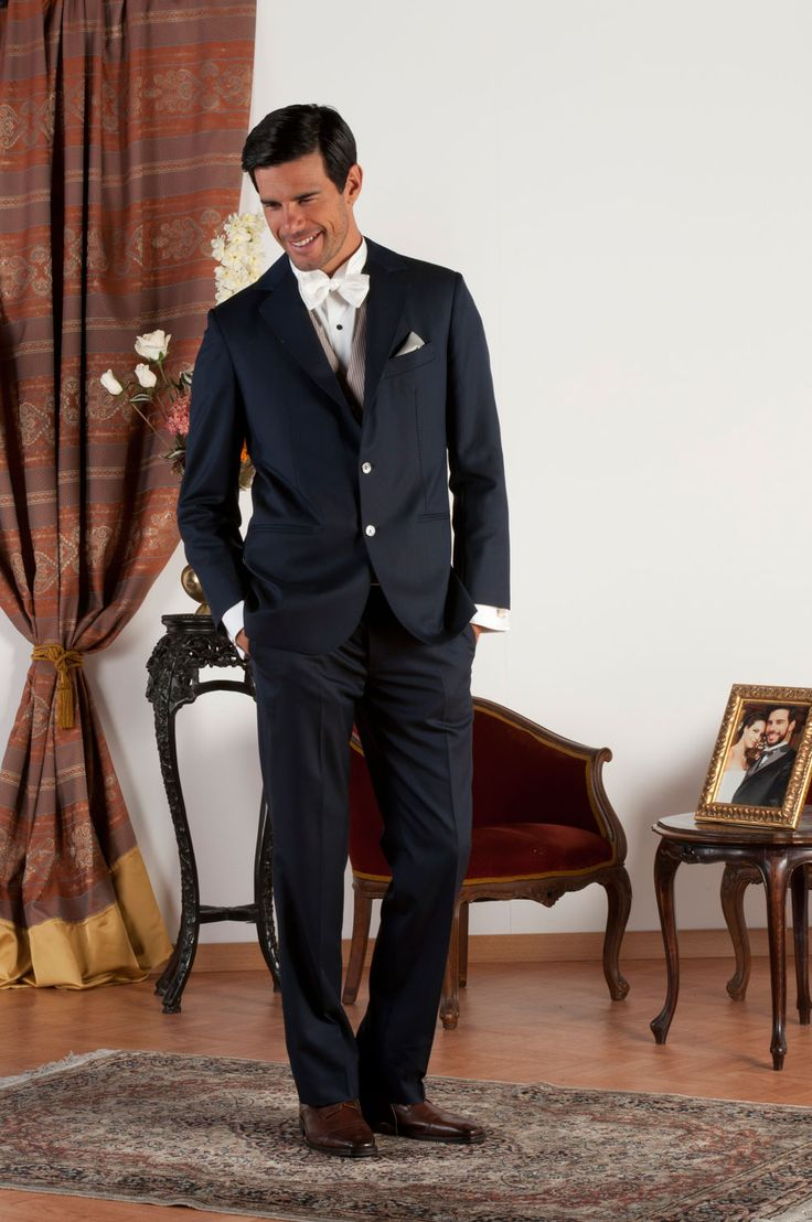 JOHN Abito sartoriale realizzato in fresco di lana blu con revers classiche, tasche a doppio filetto, gilet in jacquard di seta beige antico, bottoni in madreperla naturale.