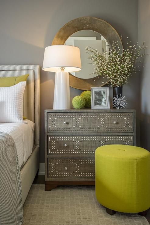 Contemporary yellow and gray bedroom features a gray wall lined with a gray pins tripe headboard with nailhead trim on bed dressed in gray chevron blankets and yellow pillows beside a Gray Raffia Chest doubling as nightstand topped with Regina Andrew White Folded Glass Lamp under a round gold mirror alongside a round canary yellow stool.
