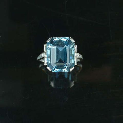 An art deco aquamarine dress ring, circa 1935, the rectangular step-cut aquamarine, to a claw mount and pierced gallery with channel-set baguette-cut diamond shoulders