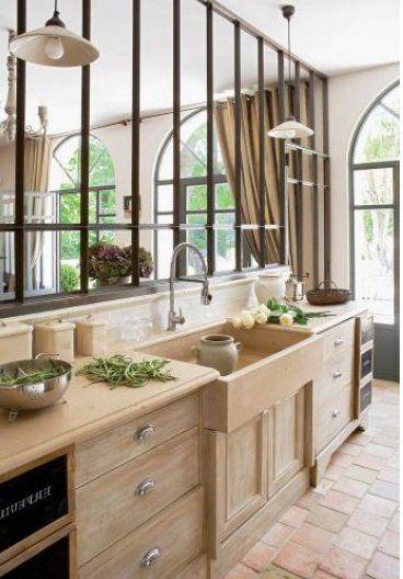 Une belle cuisine, alliance parfaite de lumière et de modernité avec la verrière en métal, et de beauté naturelle du bois, des tomettes et de l'évier à l'ancienne.
