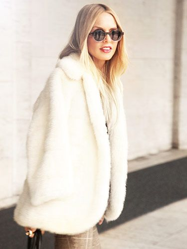 white fur jacket, sleek center-part hair, and oversized sunnies.