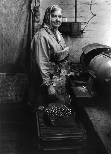"""A """"buffer girl"""" wrapped in an apron made of the Sheffield Star newspaper. Buffer girls polished the cutlery in Viners and other Sheffield cutlery factories."""