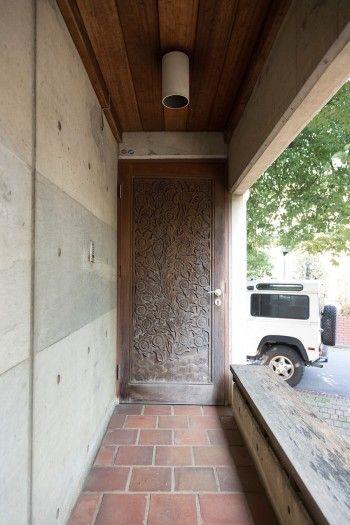 タイに学校を作るプロジェクトに参加していた際、チェンマイで彫ってもらったチークの扉を玄関のドアに。右側のベンチに腰掛けて隣人とおしゃべりもできる。