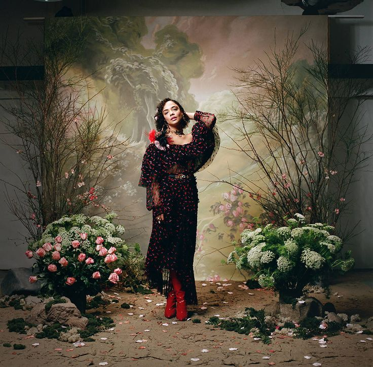 Look 8: Tessa Thompson from Rodarte Fall Winter 2018 Portrait Series  In a red and fuchsia embroidered tulle long sleeve off the shoulder blouse and a red, fuchsia and black embroidered tulle and floral hip ruffle skirt