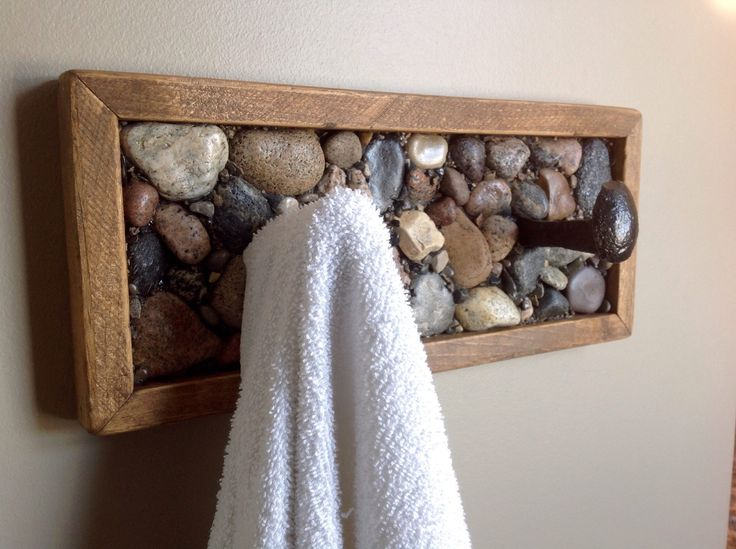 Coat rack or towel rack made from railway spikes, beach stone and rustic wood.