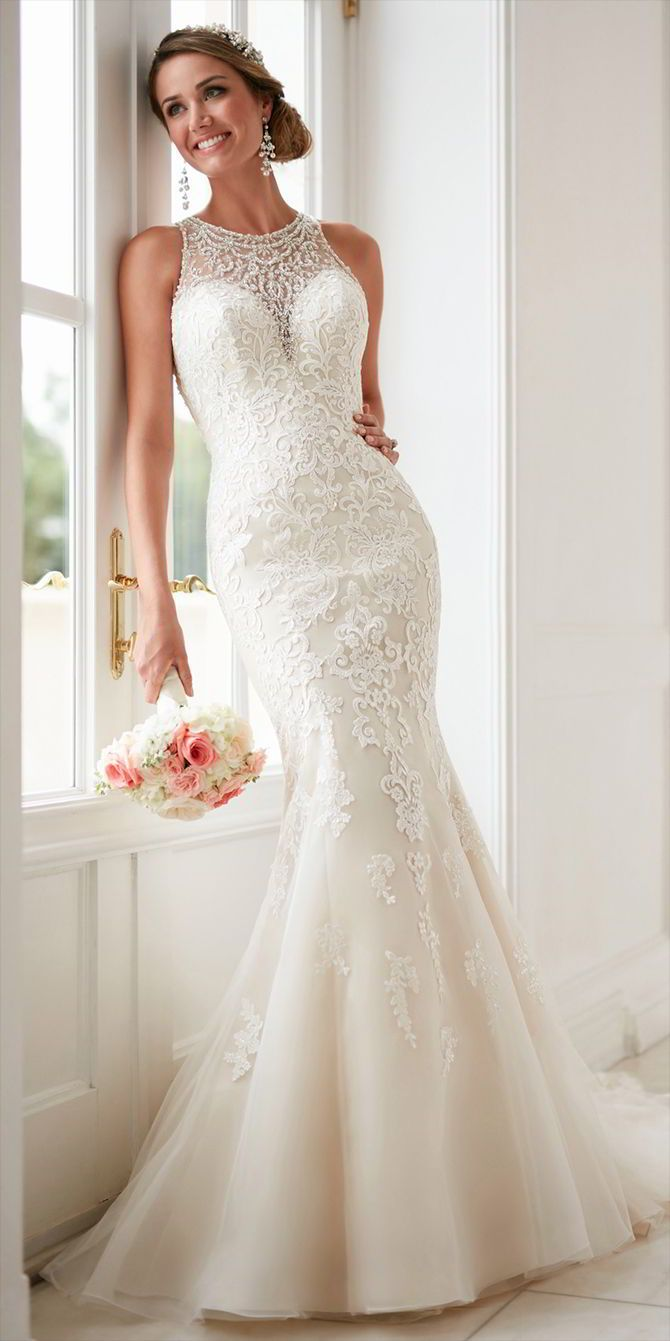 This elegant high neck wedding dress with lace beading from Stella York is an impressive fit-and-flare made for a stunning bridal moment. Lace and tulle over Regency organza creates a juxtaposition of beading and lace that brings the drama to your 'I Do's'. A deep sweetheart neckline under incredible bread work creates a waterfall effect that flows onto the bodice and into the tulle skirt which gives the illusion of an hourglass silhouette. The beautiful crystal beading continues on an…