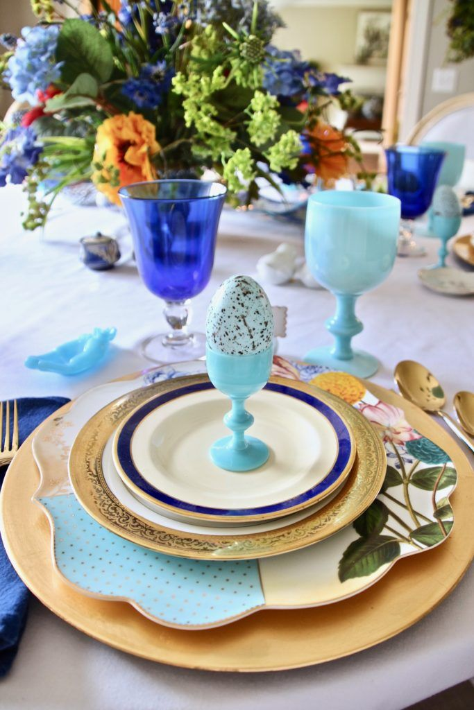 Setting the table for Easter. I took out our vintage blue milk glass. I first placed a large gold leaf charger, then the Royal Pip dinner plate,an embossed gold salad plate from my parents wedding gifts, then a cobalt blue and gold rimmed Ralph Lauren bread and butter dish, and then topped with my great-grandparents custom porcelain plates.
